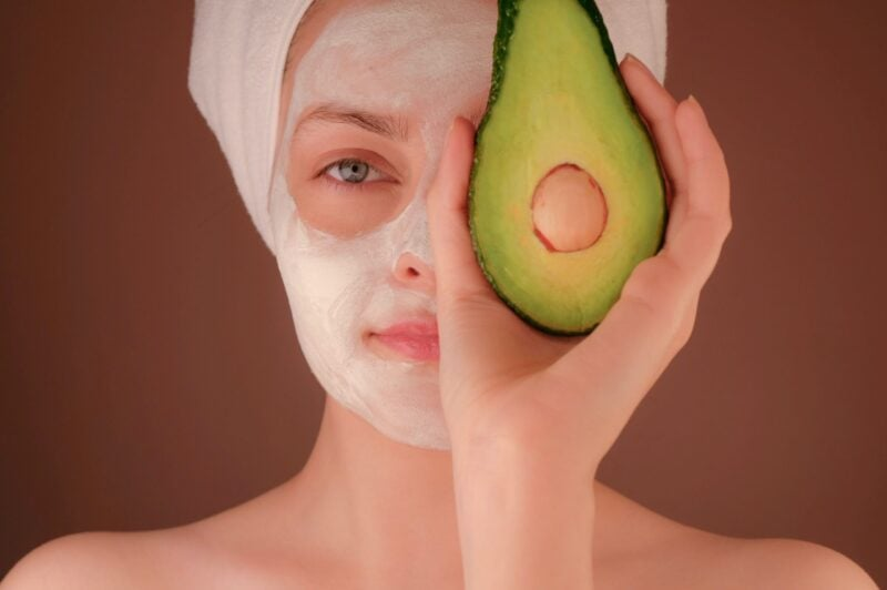 INDEPENDENT SEACRET DIRECT AGENT SKIN CARE FACIAL PRODUCTS MODEL HOLDING A AVOCADO OVER FACE WITH FACIAL SKIN PEEL APPLIED TO FACE LIFE BY SEACRET SKINCARE PRODUCTS ARE MADE WITH MINERALS FROM THE DEAD SEA.